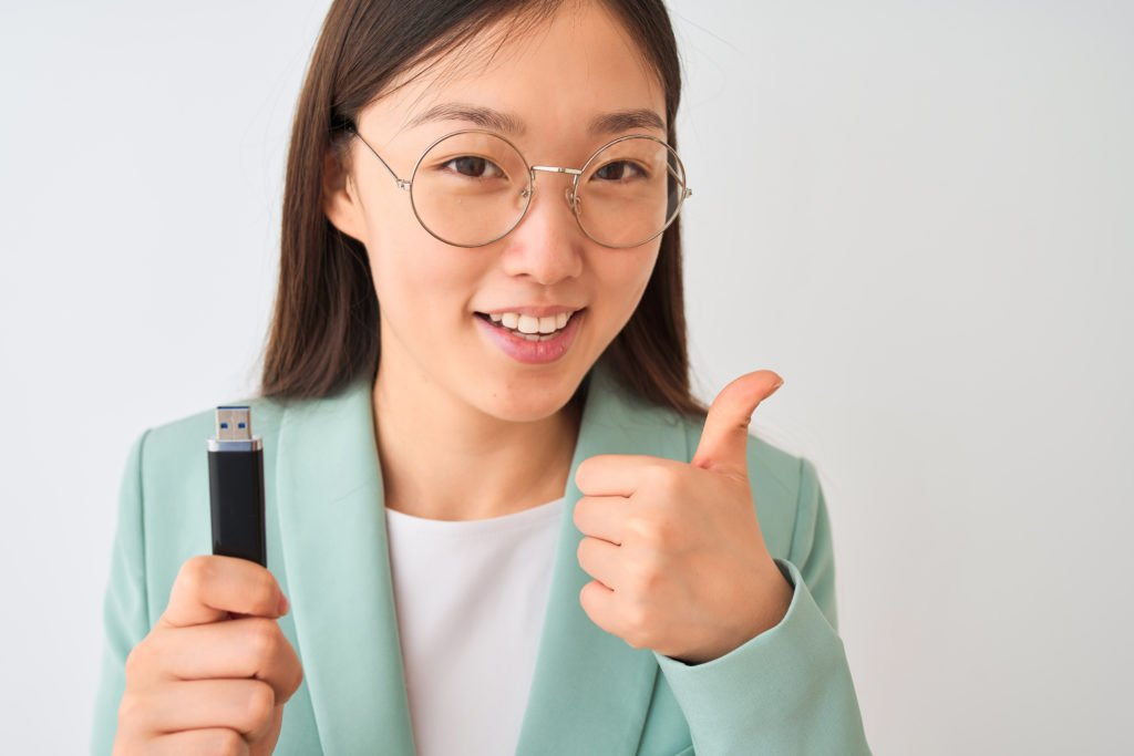 Young woman with USB flash drive, doing a thumbs up sign with her hand.