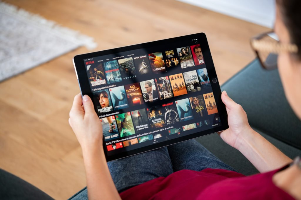 Woman watching Netflix shows on her tablet.