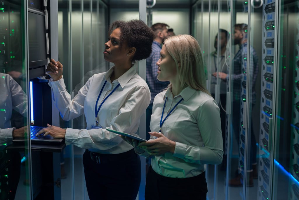 Two women working at a data center with rows of servers.