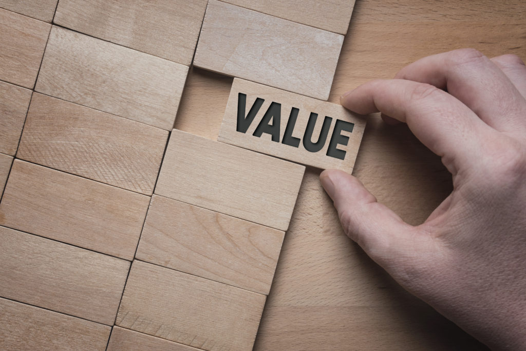 Value word written on wooden block. Add value to your business concept.