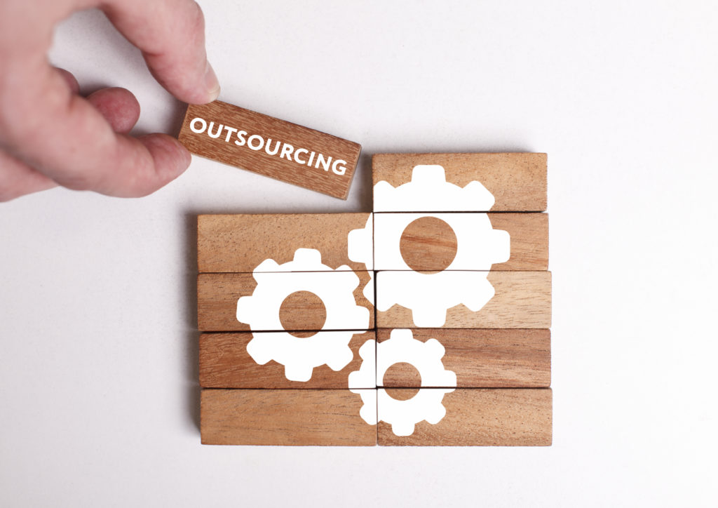 Business, Technology, Internet and network concept. Young businessman shows the word: Outsourcing.