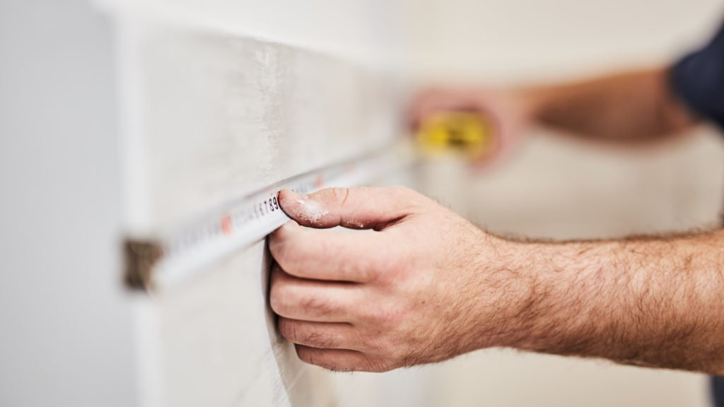Worksman using tape measure on a wall for home renovation.