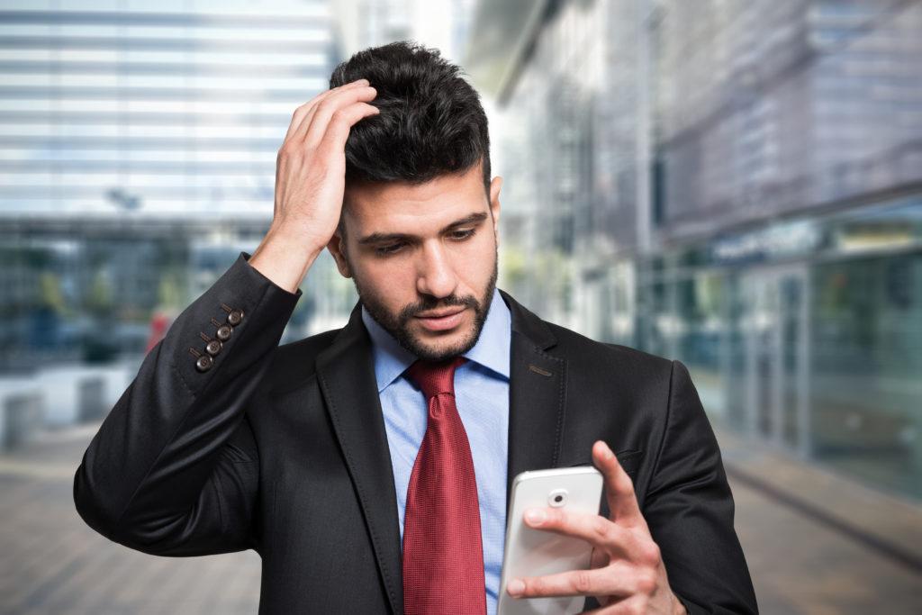 Worried businessman looking at his phone.