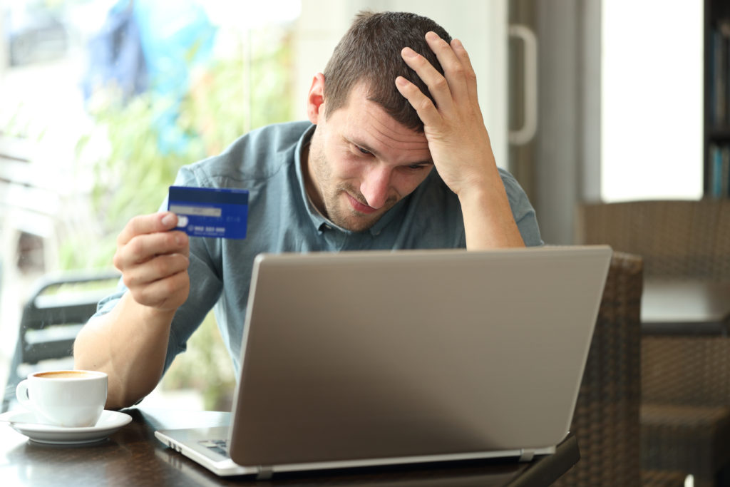 Worried man having a problem with his card, looking at his laptop.