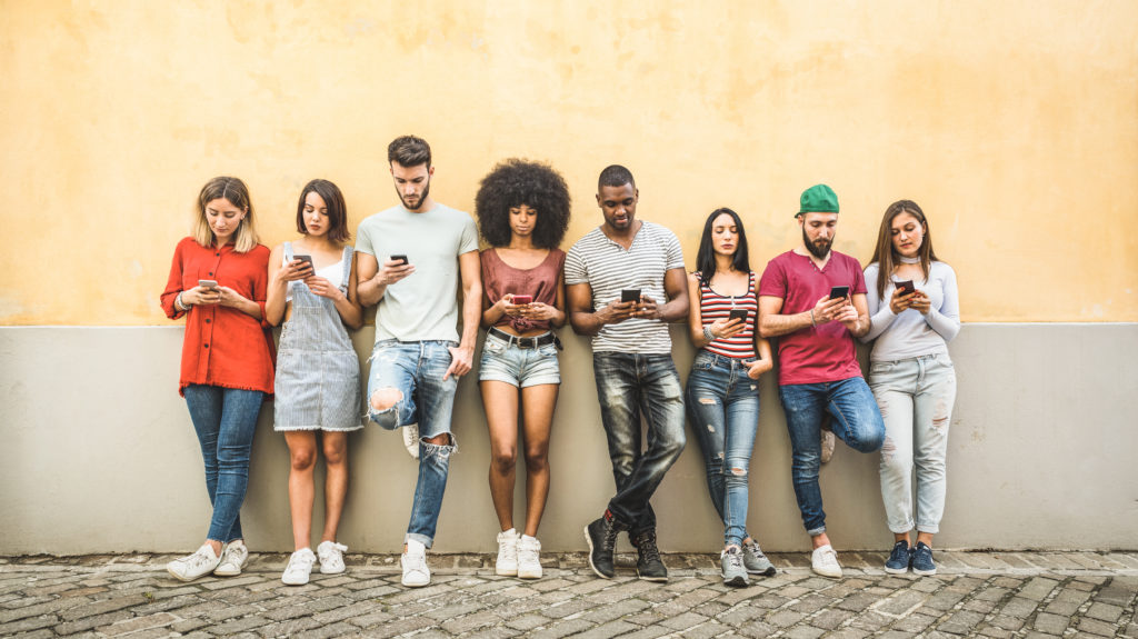 Multiracial friends using smartphone against wall at university college backyard - Young people addicted by mobile smart phone - Technology concept with always connected millennials.